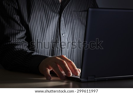 Late night internet addiction or working late man using laptop at a desk in the dark stock photo
