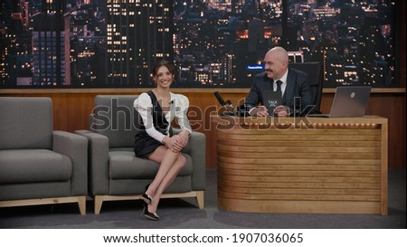 Late-night talk show host having a conversation with celebrity guest in a studio. TV broadcast style show