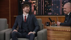 Late-night talk show host having a funny conversation with celebrity male guest in a studio. TV broadcast style show