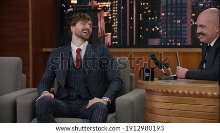 Late-night talk show host having a funny conversation with celebrity male guest in a studio. TV broadcast style show Foto d'archivio ©