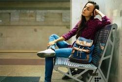 Late on train. Young woman is waiting train in subway while sitting on bench. Tired and sad woman in casual wear