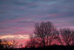 Late winter sunset created multicolor clouds behind leafless trees, intentionally under exposure.