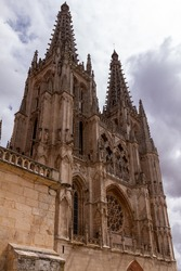 Lateral shot of Burgos' Cathedral main facade and towers against a cloudy sky