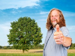 Lateral upper body view of an older long-haired man, in front of a single tree with a large treetop on summer agricultural land in the blurred background, showing thumbs up and l at the camera.