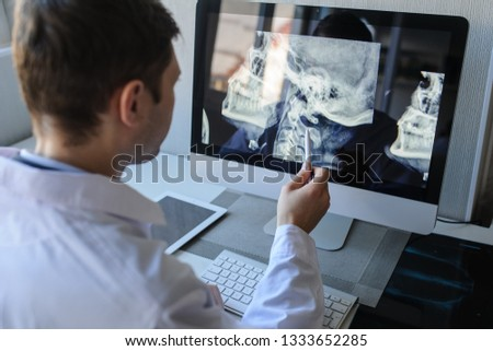 lateral view of a male radiologist examining neck x-rays (cervical vertebrae) on computer Stock photo ©