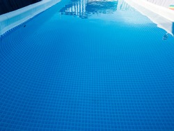 latest modern model of frame pool for children and adults in country house on flat concrete plot on gray background. Sunny summer day. concept of family holidays and active lifestyles after quarantine