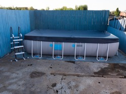 latest modern model of frame pool for children and adults in country house on flat concrete plot on gray background