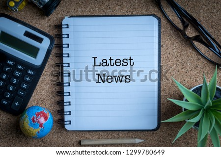 LATEST NEWS inscription written on book with globe,eyeglasses, calculator, camera, pencil and vase on wooden background with selective focus and crop fragment. Business and education concept Stock fotó ©
