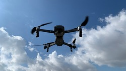 Latest technology RC camera drone or UAV (unmanned aerial vehicle) hovering on deep blue cloudy sky