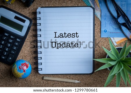 LATEST UPDATE inscription written on book with globe,eyeglasses, calculator, camera, pencil and vase on wooden background with selective focus and crop fragment. Business and education concept Stock fotó ©