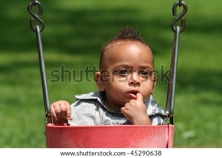 Latin African American Baby in Swing with Finger in his mouth Looking