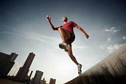 Latin american athlete running in Havana, Cuba. Horizontal shape, full length, low angle view