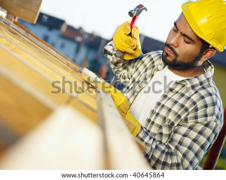 latin american construction worker on house roof with hammer. Copy space