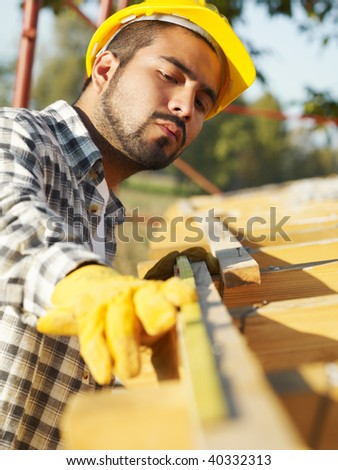 latin american construction worker on house roof with measuring tape.