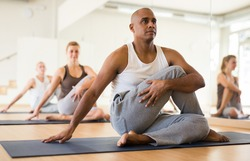 Latin american man practicing Matsyendrasana known as Lord of Fishes Pose during group yoga training