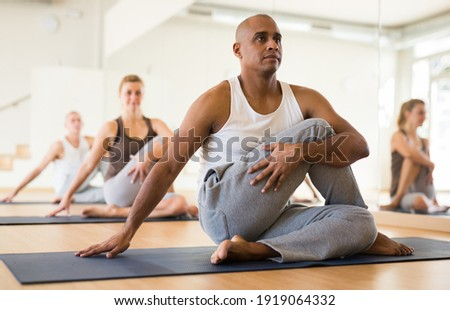 Latin american man practicing Matsyendrasana known as Lord of Fishes Pose during group yoga training Сток-фото ©