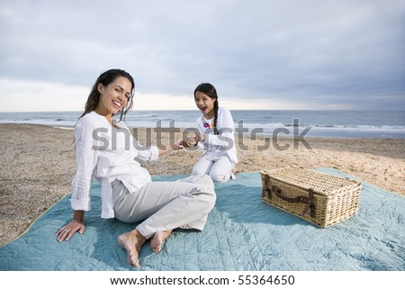 Latin American mother and 9 year old girl having picnic on beach