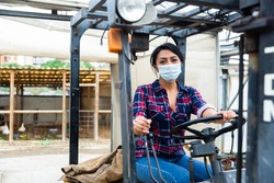 Latin american woman sits in a protective mask behind the wheel of a tractor autocar during a pandemic.