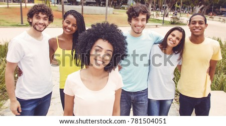 Latin american woman with group of friends in retro look outdoors in the summer