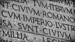 Latin ancient language and classical education. Inscription from Emperor Augustus famous Res Gestae (1st century AD), with the word Imperio in the center (Black and White)