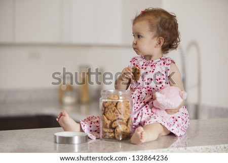 Latin baby girl eating cookies from a jar