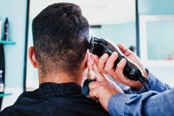 latin Barber Shop, Mexican barber cutting hair with a clipper machine or razor in Mexico City