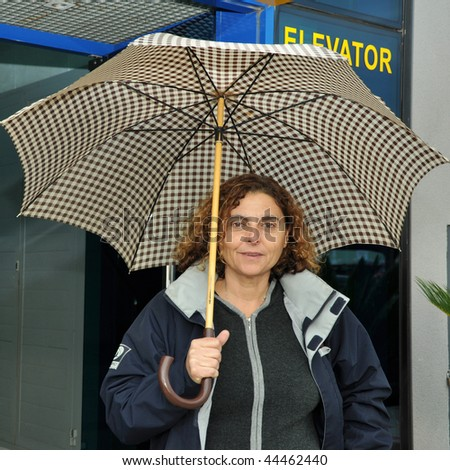 Latin business woman leaving work on a rainy day with her umbrella