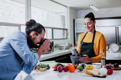 latin couple cooking mexican sauce and food taking photo in the kitchen in Mexico city