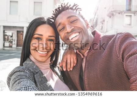 Latin couple taking selfie photo for social network story - Influencers people having fun with new trend technology - Love, fashion and relationship concept - Focus on faces