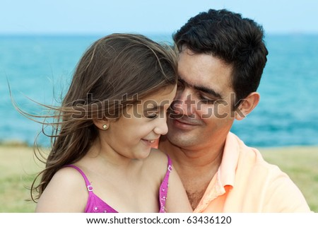 Latin daughter and father smiling and looking at each other by the seaside