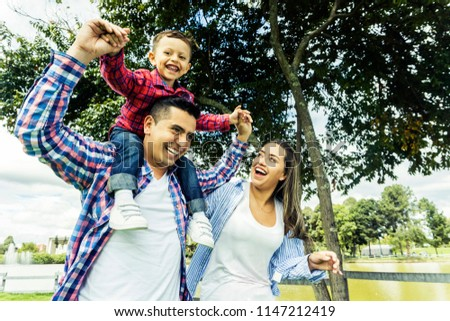 Latin family having fun at the park in the morning #1147212419