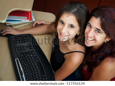 Latin girl and her beautiful mother working on a computer at home ( Image taken from above with the subjects looking at the camera)