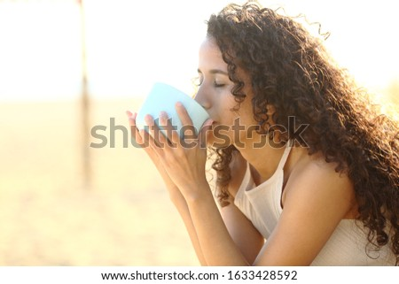 Latin girl drinking coffee with closed eyes enjoying flavor on the beach