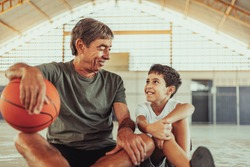 Latin grandfather and grandson playing basketball on the court