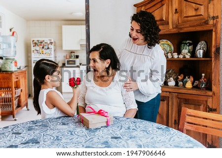 latin grandmother woman with daughter or grandchild celebrating birthday, 8 March International women holiday or Happy Mother's Day in Mexico city