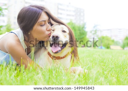 Latin Hispanic brunette young girl kissing her white dog in the city park on the background of the house Copy space for inscription