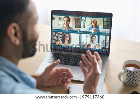 Latin indian businessman having virtual team meeting group call chatting with diverse people in customer support. Video conference call on computer with manager and employees. Over shoulder view.