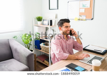 Latin man in his 20s is at his home office working as a salesman and happily talking on the phone with a customer