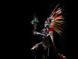 Latin man with death makeup, catrin, dressed as an Aztec god with a clay fret with incense and fire, body paint of bones, a plume of colored feathers and prehispanic costume, day of the dead
