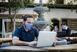 latin man working with computer wearing face mask for social distancing in new normal situation protecting and preventing the infection of corona virus or covid-19, mexican coworkers in Mexico city