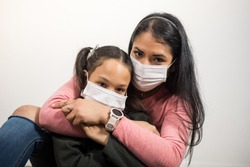 Latin mother and daughter hug each other and wearing medical mask on white background.Family wearing mouth mask against air smog pollution.Concept of fear coronavirus quarantine or covid-19 infection.