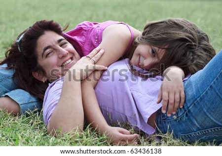 Latin mother and daughter lying down and smiling in a green grass field