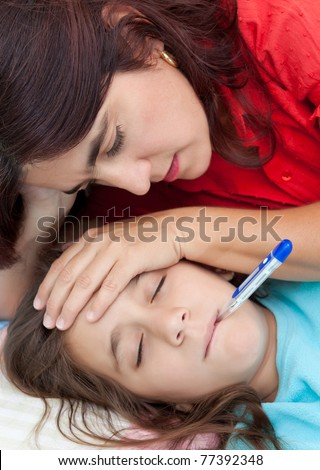Latin mother checking the temperature of  her sick daughter who has a thermometer in her mouth