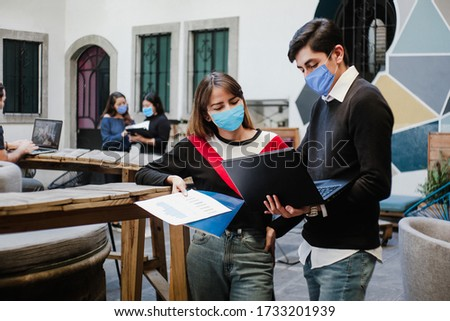 Latin people teamwork working in coworking while wearing face mask for social distancing in new normal situation preventing the infection of corona virus or covid-19, Mexican Coworkers in Mexico