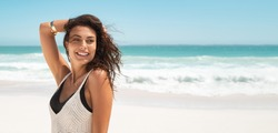 Latin stylish woman relaxing at tropical beach during summer vacation. Portrait of carefree tanned girl relaxing at sea with copy space. Young smiling woman enjoying breeze and looking away.