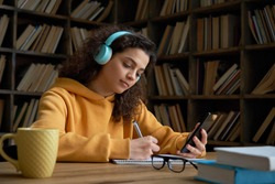 Latin teen girl wear headphones hold phone online learning in mobile app. Hispanic college student using smartphone watching video course, zoom calling making notes in workbook sit in library campus.
