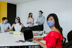 Latin woman and teamwork working in business office while wearing face mask for social distancing in new normal situation preventing the infection of corona virus or covid-19 Mexican People