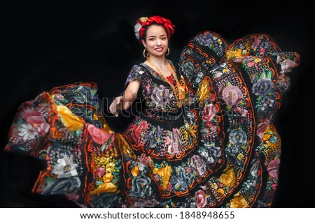 Latin woman dressed as Chiapas with a costume embroidered with flowers, a bow braid and a shawl, Mexican dancer, multicolored traditional folklore ストックフォト ©