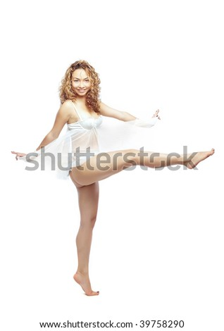 Latin woman with curly hairs swinging her leg and dancing in white peignoir