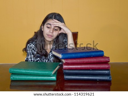 Latin young girl stressed by much studying to do